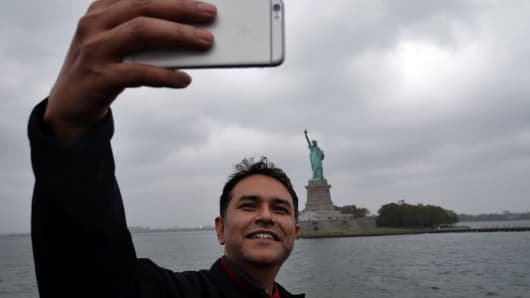 A tourist takes a selfie with the Statue of Liberty as cloud hover over it in New York.