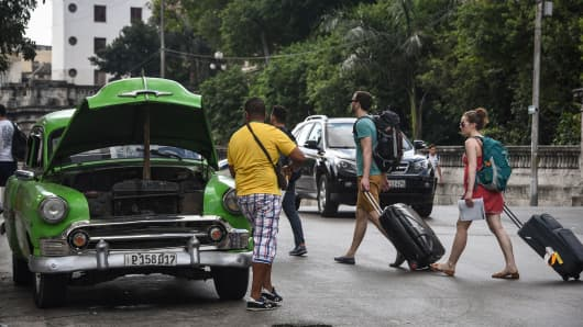 A man repairs his car as tourists walk past in Havana, Cuba.