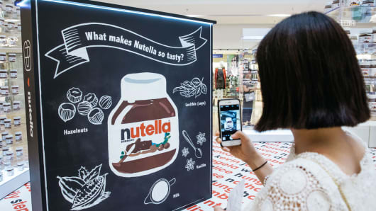 A woman takes a photograph using a smartphone at a Ferrero SpA's Nutella pop up store inside Pacific Place shopping mall in the Admiralty district of Hong Kong.