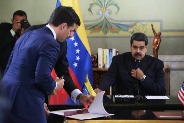Horizontal Well Drillers CEO Todd Swanson signs a memorandum of understanding with Venezuela's state-run oil company as President Nicolás Maduro looks on.