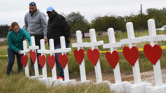People unload crosses outside the First Baptist Church which was the scene of the mass shooting that killed 26 people in Sutherland Springs, Texas on November 8, 2017.
