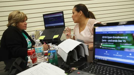 An insurance agent from Sunshine Life and Health Advisors, speaks with a woman shopping for insurance under the Affordable Care Act at a store setup in the Mall of Americas on November 1, 2017 in Miami, Florida.