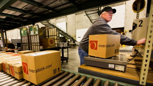 An employee scans an order in the shipping area at the Overstock.com distribution center in Salt Lake City, Utah.