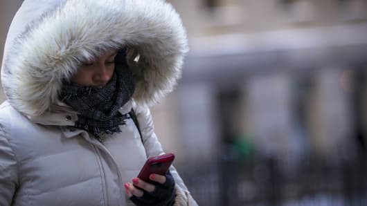 A woman checks her phone as she walks on Wall St. during the morning commute in New York's financial district January 22, 2014