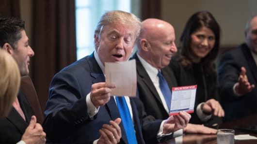 US President Donald Trump looks at a sample of the proposed new tax form at the White House in Washington, DC, on Nov. 2, 2017.