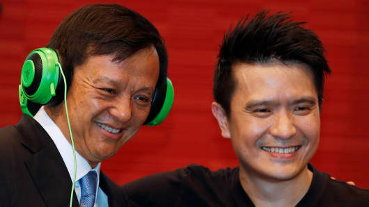 Hong Kong Exchanges Chief Executive Charles Li, wearing Razer headphones, poses with Min-Liang Tan, CEO of Razer, during the debut of the company at the Hong Kong Exchanges in Hong Kong on Nov. 13, 2017.