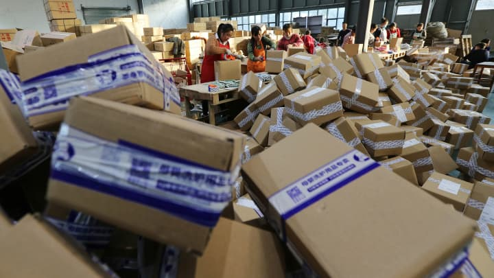 Workers distribute express parcels at a logistics centre of China Post during Alibaba Group's Singles' Day global shopping festival on November 11, 2016 in Ganyu, China.