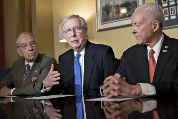 Senate Majority Leader Mitch McConnell, a Republican from Kentucky, center, speaks as Senator Orrin Hatch, a Republican from Utah and chairman of the Senate Finance Committee, right, and Senator Chuck Grassley, a Republican from Iowa, listen during a meeting with members of the committee on tax reform legislation at the U.S. Capitol in Washington, D.C., on Thursday, Nov. 9, 2017.