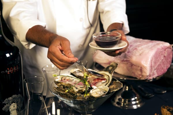 A chef pours Opus One mignonette over $100 imported king oysters.