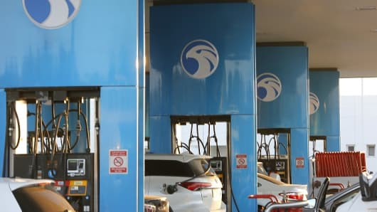 ADNOC distribution service station pumps with logo in daylight.