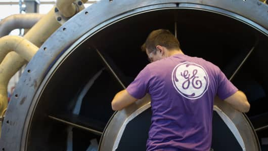 An employee of General Electric works on a gas turbine at the GE plant in Belfort, France.