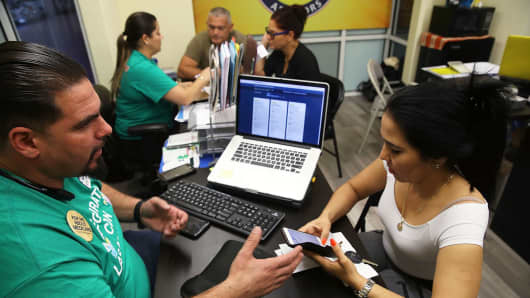 Ulysses Hernandez (L), an insurance agent from Sunshine Life and Health Advisors, speaks with Yuricel Duran as she shops for insurance under the Affordable Care Act at a store setup in the Mall of Americas on November 1, 2017 in Miami, Florida.