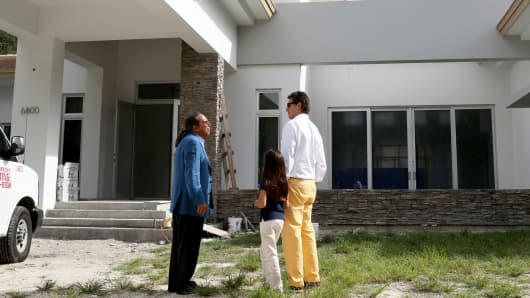 A real estate consultant from Re/Max Advance Realty shows a new home to a prospective buyer in Miami, Florida.