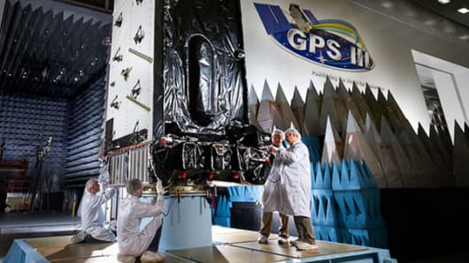 Workers at a Lockheed Martin facility in the Denver area inspecting the company's GPS III SV1 satellite in an environmentally clean testing chamber.