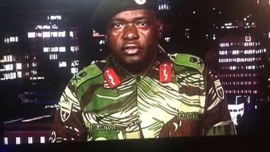 This screen grab taken early on November 15, 2017 from a television broadcast on the Zimbabwe Broadcasting corporation (ZBC) shows Zimbabwe Major General Sibusiso Moyo reading a statement at the ZBC broadcast studio in Harare. Zimbabwe's military appeared to be in control of the country on November 15 as generals denied staging a coup but used state television to vow to target