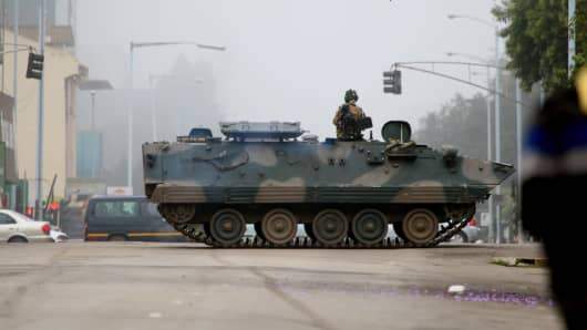A military tank seals off a main road to the presidential office within the military activities taking place in Harare, Zimbabwe on November 15, 2017