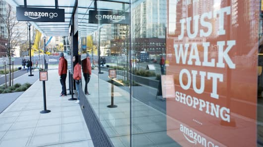 Employees stand outside the new Amazon Go grocery store in Seattle, Washington.