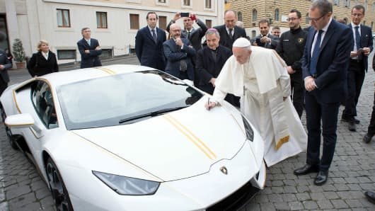 Pope Francis writes on the bonnet of a Lamborghini donated to him by the luxury sports car maker, at the Vatican, Wednesday, Nov. 15, 2017. The car will be auctioned off by Sotheby's, with the proceeds going to charities including one aimed at helping rebuild Christian communities in Iraq that were devastated by the Islamic State group.