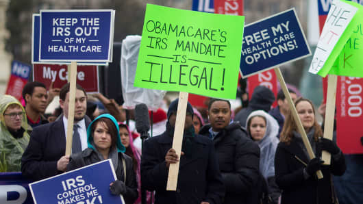 Demonstrators opposed to U.S. President Barack Obama's health-care law, Obamacare, hold signs in front of the U.S. Supreme Court in Washington, D.C., U.S., on Wednesday, March 4, 2015.