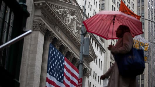 A pedestrian holds an umbrella while walking past the New York Stock Exchange.