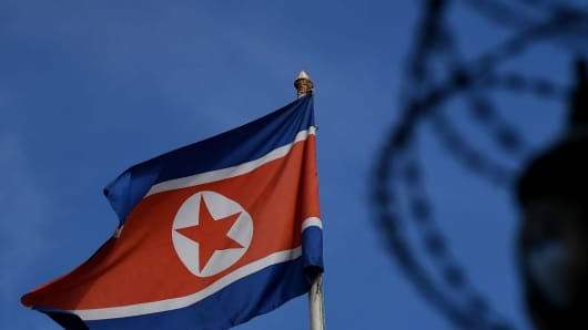 The North Korean flag is seen at mast past barbed wire fencing.