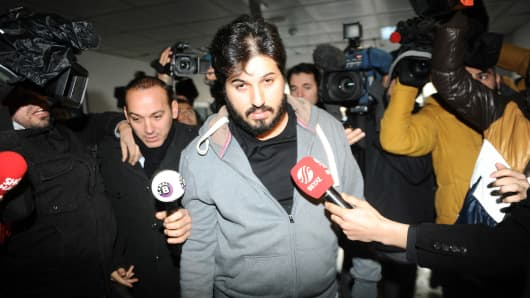 Detained Azerbaijani businessman Reza Zarrab (C) is surrounded by journalists as he arrives at a police center in Istanbul on December 17 ,2013.