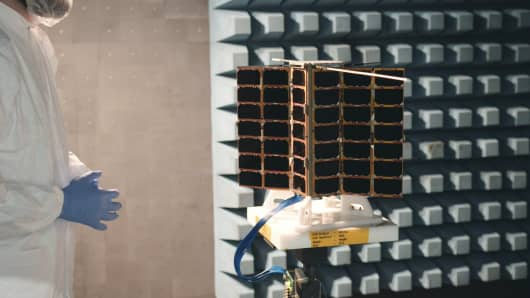 Spire employees testing a small, weather-tracking satellite.