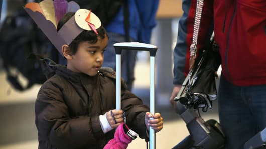 A child waits as his parents check in for a flight at O'Hare International Airport in Chicago, Illinois.