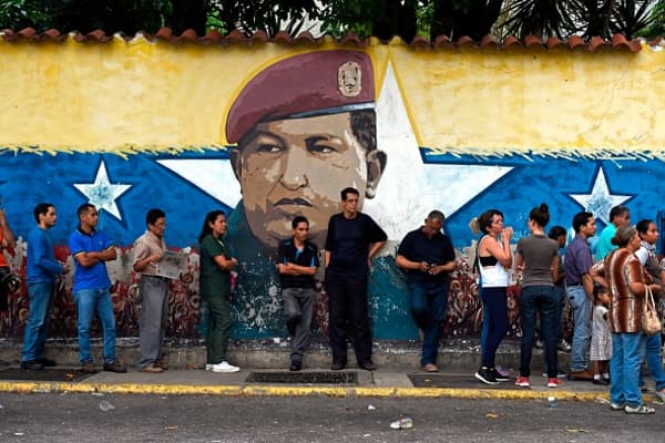 Venezuelans queue outside a polling station as they wait to cast their vote during regional elections in Caracas, Venezuela on October 15, 2017.