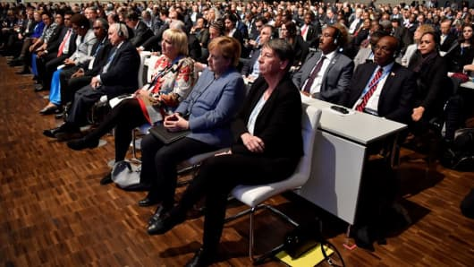 German outgoing Environment Minister Barbara Hendricks, Chancellor Angela Merkel and member of the Greens party Claudia Roth listen to French president's speech during the UN conference on climate change (COP23) on November 15, 2017 in Bonn, western Germany.