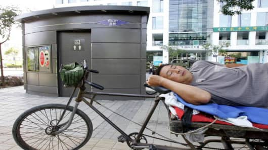 A vendor takes a nap beside a public 'bomb-proof' toilet in Beijing's Zhongguancun 'Silicon Valley' area, 06 September 2006. It was reported 06 September that the toilet, which has received a fair amount of interest in the Chinese and Hong Kong press, cost over 800,000 yuan (100,000 USD), has 30cm (10 inch) thick walls and features automatic flushing and sterilising. According to Hong Kong's South China Morning Post, who quoted a top city criminal investigator, the toilet could be strong enough to protect users from a bomb blast.