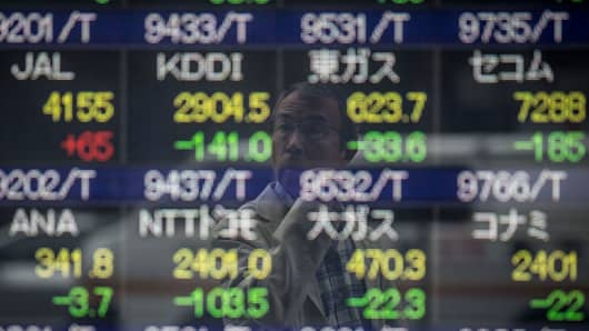 A man looks at a screen showing global stock market information on the street in Tokyo, Japan.