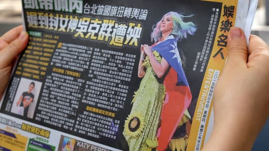 In this photo taken on April 30, 2015, a local resident reads a newspaper showing U.S. singer Katy Perry wearing Taiwan's national flag in the capital Taipei.