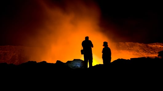 A couple of scientists standing on the crater rim of Erta Ale - one of the most active vulancoes in the world with an active, red glowing lava lake.