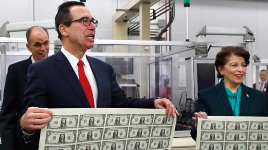 Treasury Secretary Steven Mnuchin and U.S. Treasurer Jovita Carranza, right, hold up sheets of new $1 bills, the first currency notes bearing Mnuchin and Carranza's signatures, Wednesday, Nov. 15, 2017, at the Bureau of Engraving and Printing in Washington.