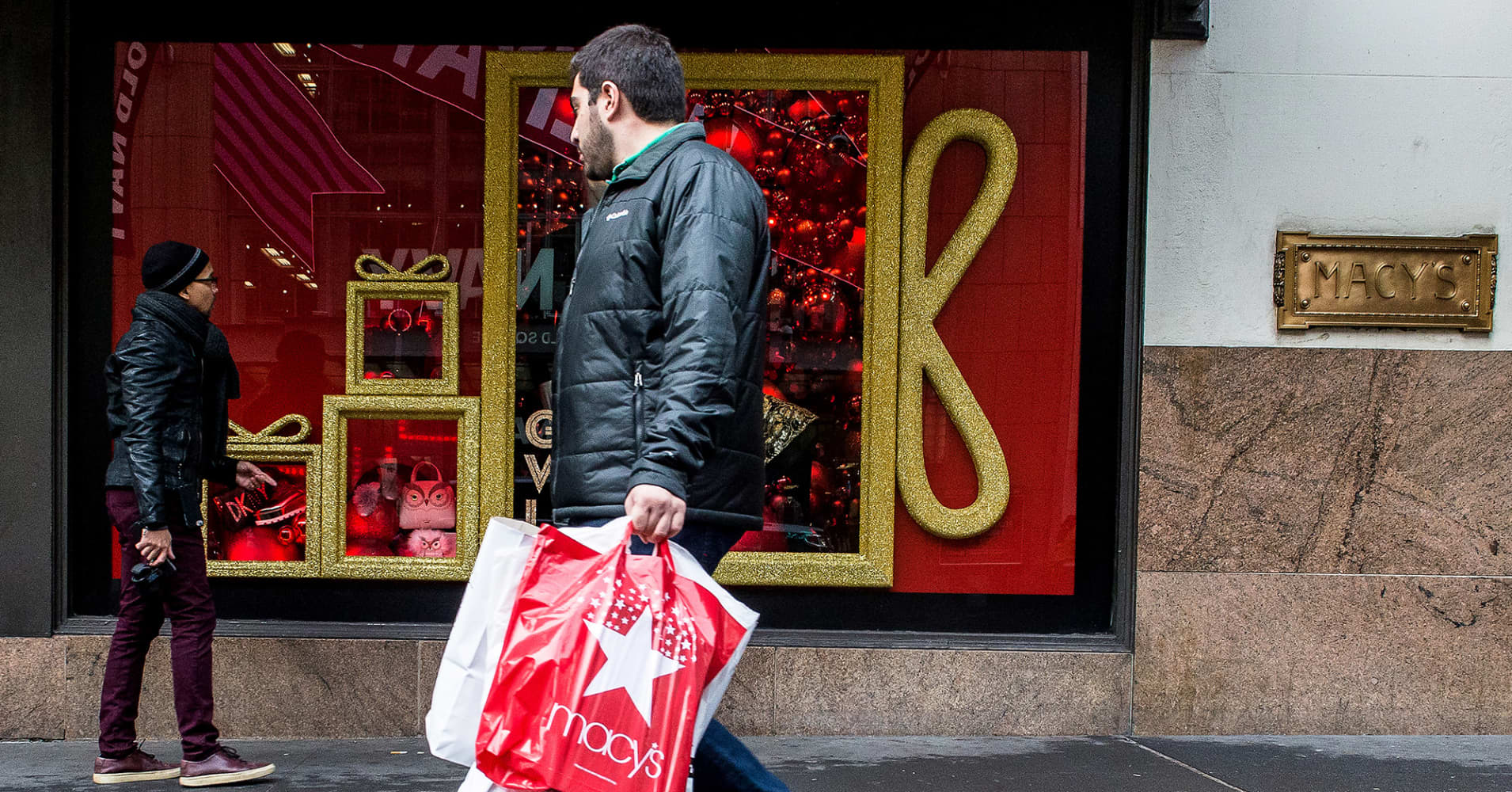 A pedestrian carries a Macy's Inc. shopping bag while walking past a store in New York.