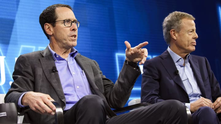 Randall Stephenson, chairman and chief executive officer of AT&T Inc., left, speaks while Jeffrey 'Jeff' Bewkes, chairman and chief executive officer of Time Warner Inc., listens during the WSJDLive Global Technology Conference in Laguna Beach, California.