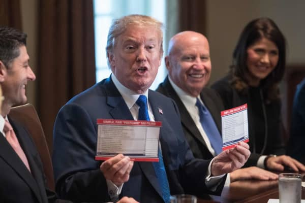 President Donald Trump shows samples of the proposed new tax form at the White House in Washington, DC, on November 2, 2017.