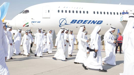 Sheikh Mohammed bin Rashid Al Maktoum, United Arab Emirates vice president and prime minister, center blue sandals, passes a Boeing Co. 787-10 passenger aircraft, operated by Emirates Airlines, during the 15th Dubai Air Show at Dubai World Central (DWC) in Dubai, United Arab Emirates, on Monday, Nov. 13, 2017.
