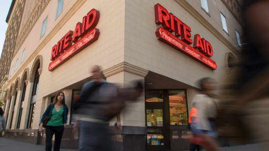 Pedestrians walk past a Rite Aid Corp. store in Oakland, California.