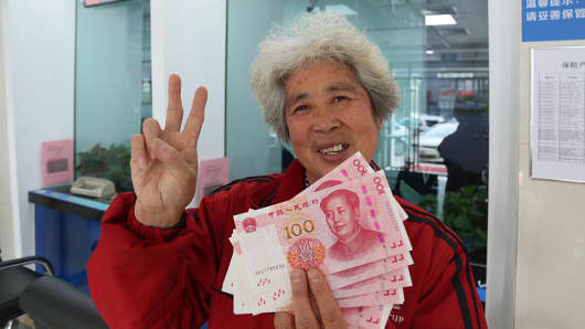 A citizen shows new 100 yuan notes she withdrew at a counter of China Construction Bank in the Hangzhou province of China.