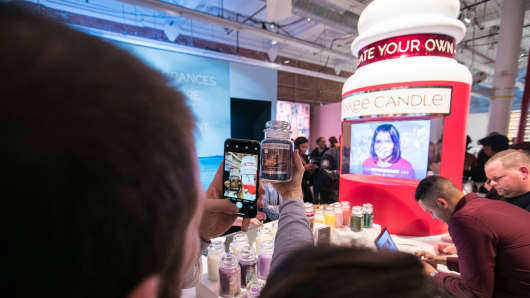 Someone photographs a personalized candle at Yankee Candle's pop-up shop in New York City.
