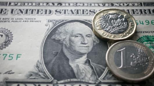 A U.S. dollar bill, £1 coin and 1 euro coin