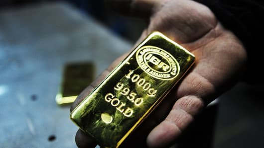 A worker holds a gold bullion at Istanbul Gold Refinery on January 13, 2015, in Istanbul, Turkey.