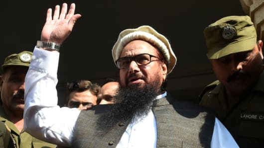 Pakistan head of the Jamaat-ud-Dawa (JuD) organisation Hafiz Saeed waves to supporters as he leaves a court in Lahore on November 21, 2017.