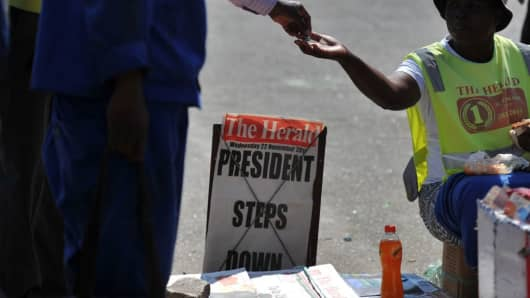 A man buys a newspaper at a stand on a street corner in Harare on November 22, 2017, the day after the resignation of President Robert Mugabe who ruled for 37 years last night.