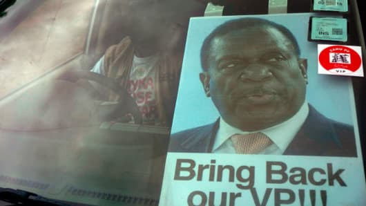 A man takes part in a demonstration demanding the resignation of Zimbabwe's president with a sign featuring deputy president Emmerson Mnangagwa in the windshield of his car on November 18, 2017 in Harare.