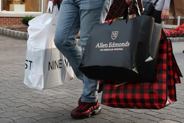 A man walks with bags from the Nine West, Allen Edmonds and Woolrich stores at the Woodbury Common Premium Outlets Mall on October 21, 2017 in Central Valley, NY.