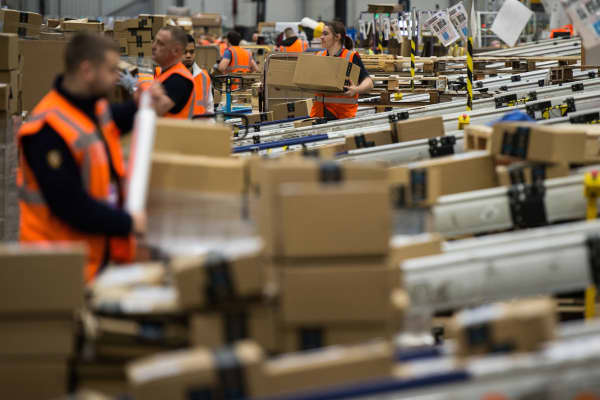 Workers prepare customer orders for dispatch as they work around goods stored inside an Amazon.co.uk fulfillment centre.