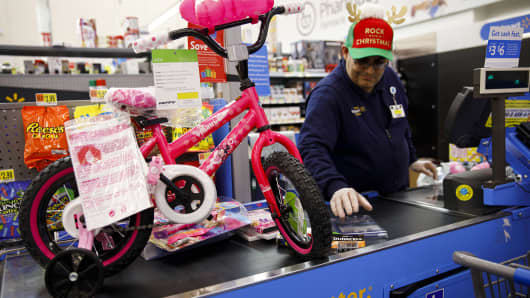 An employee prepares to scan a children's bicycle for a customer at a Wal-Mart Stores Inc. location in Burbank, California, U.S., on Thursday, Nov. 16, 2017.
